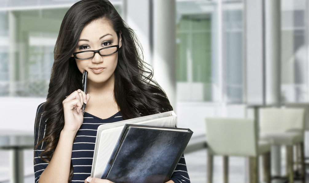 Young asian female student with books, making a confused expression, interior background